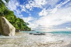 Tropischer Strand des Paradieses mit Felsen, Palmen und Türkis wate Stockfotografie