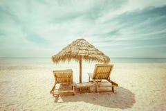 Tropischer Strand mit decken Regenschirm und Stühle für Entspannung mit Stroh lizenzfreies stockfoto