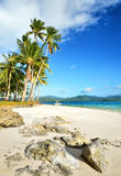 Tropischer Strand mit einem Boot auf einem Hintergrund von Gebirgsinseln Stockbilder
