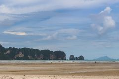 Tropischer Strand mit Klippen und Inseln im Horizont stockbilder
