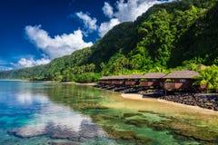 Tropischer Strand mit mit KokosnussPalmen und Strandhäusern an Lizenzfreies Stockfoto