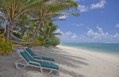 Tropischer Strand mit Palmen und Aufenthaltsraum-Stühlen Stockfotografie