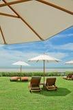 Tropischer Strand mit Regenschirm und Stühlen Lizenzfreie Stockbilder