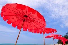 Tropischer Strand mit roten Regenschirmen Stockbild