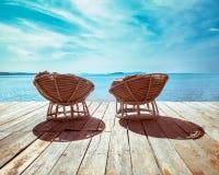 Tropischer Strand mit Stühlen auf hölzerner Terrasse Stockbild