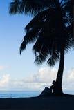 Tropischer Strand, Palme mit sitzender Frau, Schattenbild Stockfotografie