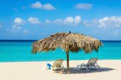 Tropischer Strand, sunbeds und Palmeregenschirme Stockfotos