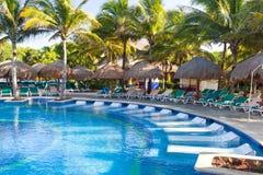 Tropischer Swimmingpool mit sunbeds Lizenzfreie Stockfotografie