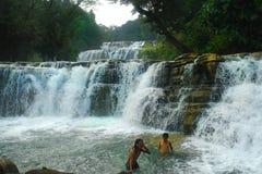 Tropischer Wasserfall, schwimmende Jungen. Lizenzfreie Stockfotografie