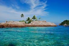 Tropisches blaues Meer mit kleiner Insel mit Palme stockfotos