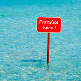 Tropisches Meer des Türkises mit dem roten Zeichen, das hier Paradies sagt Stockfotografie