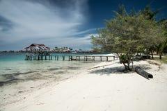 Tropisches Sandstrandurlaubsort auf Fern-Malenge-Insel, Teil von Togean-Archipel mit traditionellen Booten stockbilder