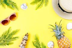 Tropisches Sommerkonzept mit Frauenmode-accessoires, -blättern und -ananas auf gelbem Hintergrund Flache Lage, Draufsicht Lizenzfreies Stockfoto
