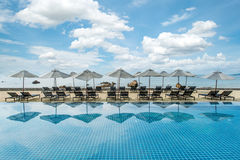 Tropisches Strandurlaubsort mit Klubsesseln und Regenschirmen in Phuket, Thailand Lizenzfreies Stockfoto