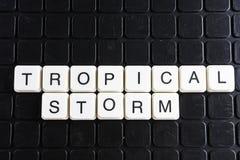 Tropisches Sturmtext-Wortkreuzworträtsel Alphabetbuchstabe blockiert Spielbeschaffenheitshintergrund Schwarzer Hintergrund Stockfoto