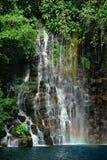 Tropisches Wasserfalldetail mit Regenbogen. Lizenzfreies Stockbild