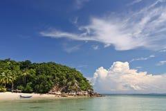 Tropisk ö med det klara blåa havet och fartyg på den vita stranden royaltyfri foto
