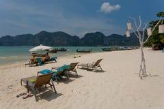 Tropisk ö med semesterorter och sandig strand med vardagsrumstolar Royaltyfria Bilder