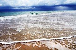 Tropisk farlig storm över havvattenstranden Arkivfoto