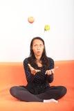 Tropisk flicka som jonglerar med äpplet och päronet Royaltyfri Foto