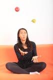 Tropisk flicka som jonglerar med äpplet och päronet Royaltyfria Bilder