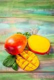 Tropisk frukt f?r mango p? en m?rk tr?bakgrund Lekmanna- l?genhet placera text olivgr?n f?r olja f?r k?k f?r kockbegreppsmat ny ? royaltyfri fotografi