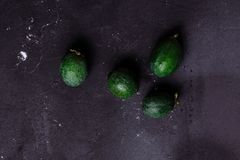 Tropisk frukt, rå organisk grön feijoa på en mörk svart bakgrund, kopieringsutrymme sund mat arkivbild