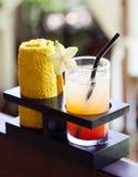 Tropisk fruktsaft och förkylninghandduk, välkommen drink i hotellet och utomhus- bakgrund för brunnsort Royaltyfri Foto