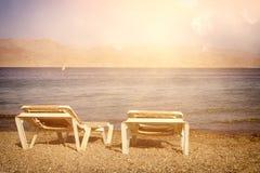 tropisk havsstrand och dagdrivare för två chaise på solnedgångljus Sommarlopp och semesterbegrepp royaltyfria bilder