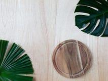 Tropisk monstera och palmblad, skärbräda för runt trä på den wood bakgrunden arkivbild