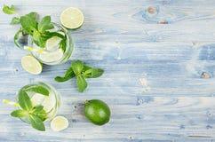 Tropisk ny kall coctailginuppiggningsmedel med mintkaramellen, limefrukt, is, sugrör på ljus - blått sjaskigt wood bräde, gräns,  royaltyfri fotografi