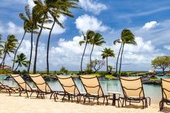 Tropisk paradisplats med rad av stolar längs en sandig strand w Fotografering för Bildbyråer