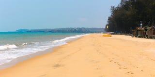 Tropisk sandig strand av havet med vågor och solig himmel Arkivbilder