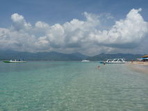 Tropisk sandig strand med fartyg och blått vatten Arkivfoto