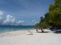 Tropisk sandig strand med fartyg, träd och blått vatten Arkivbild