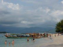 Tropisk sandig strand med träd, fartyg och blått vatten Arkivfoto