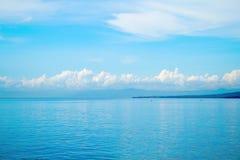 Tropisk seascape med den avlägsna ön och blå himmel Avslappnande havssikt med stilla havsvatten Arkivbild