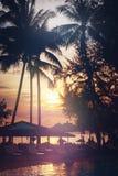 tropisk sikt för strand Palmträd och solnedgånghimmel Royaltyfri Foto