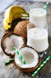 Tropisk smoothiedrink för kokosnöt med bananer på träbackgroun arkivfoto