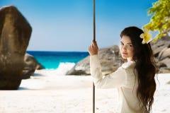 tropisk strand Attraktiv le stående för brunettflickasommar Royaltyfria Bilder