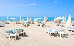 Tropisk strand av Alanya Solsängar och deckchairs på det sandiga havet sätter på land på solig solig dag Resa resväskan med seasc Arkivbilder