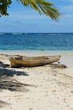 Tropisk strand med dugoutkanoten på sand Arkivbilder