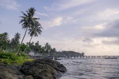 Tropisk strand med palmträd i fiskarebyn arkivbilder