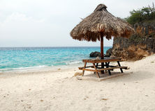 Tropisk strand med picknickbänken och slags solskydd på Curacao Arkivbilder