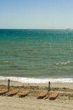 Tropisk strand med stolar arkivbilder