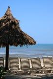 Tropisk strand med stolar Arkivfoto