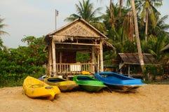 Tropisk strandinställning med kokospalmer, kojan och säng. Arkivbilder