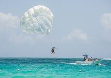 Tropisk strandparasailing med vitsander och blått vatten Royaltyfria Bilder