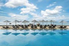 Tropisk strandsemesterort med vardagsrumstolar och paraplyer i Phuket, Thailand Royaltyfri Foto