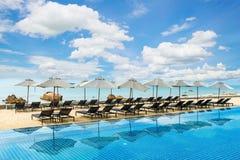 Tropisk strandsemesterort med vardagsrumstolar och paraplyer i Phuket, Thailand Arkivbild